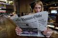 米ボストンの駅でボストン・グローブ紙を読む女性(2018年8月15日撮影)。(c)AFP / Joseph PREZIOSO
