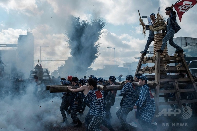 愛知県豊橋市で、手筒花火を吉田神社まで担ぐ男性たち(2018年7月20日撮影)。(c)AFP PHOTO / Yasuyoshi CHIBA