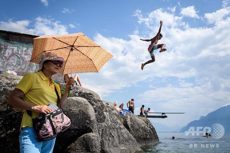 欧州一帯を熱波が覆っている。スイス西部サンサフォランのレマン湖に飛び込む少年(2018年7月31日撮影)。(c)AFP PHOTO / Fabrice COFFRINI