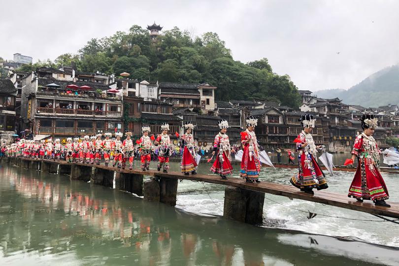 鳳凰古城を流れる沱江の橋を渡る盛装したミャオ族の女性(2019年10月27日撮影)。(c)Xinhua News