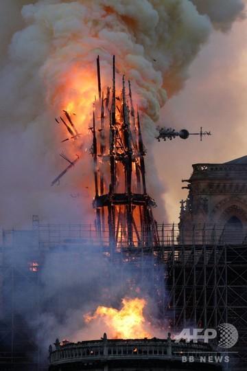 パリで、火災により崩壊する観光名所ノートルダム寺院の尖塔(2019年4月15日撮影)。(c)Geoffroy VAN DER HASSELT / AFP