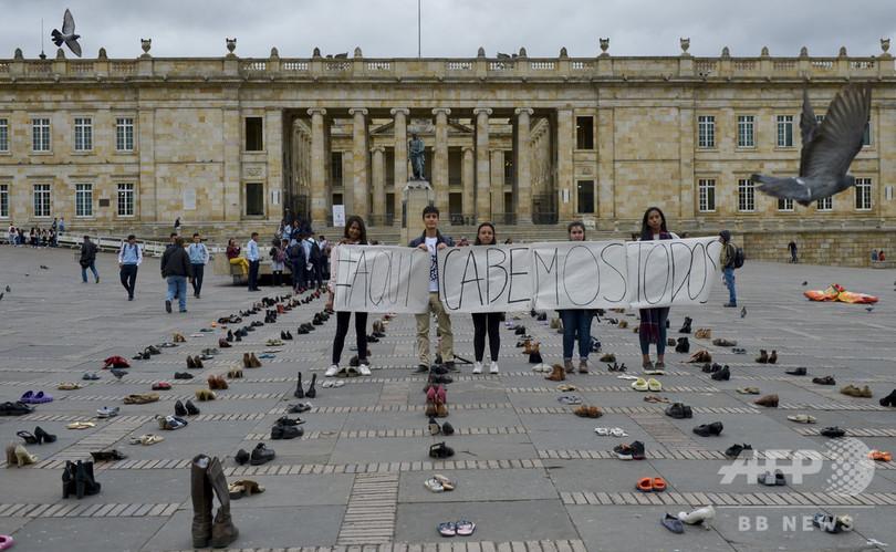 ベネズエラ移民の靴が並べられたコロンビアの首都ボゴタのボリバル広場で、「私たちは皆ここでぴったりなじむ」と書かれたバナーを持つ活動家ら(2019年9月13日撮影)。(c)Raul ARBOLEDA / AFP