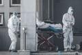 中国中部・武漢市で、新型コロナウイルスによる感染者が治療を受ける病院に患者を搬送する医療関係者(2020年1月18日撮影)。(c)AFP