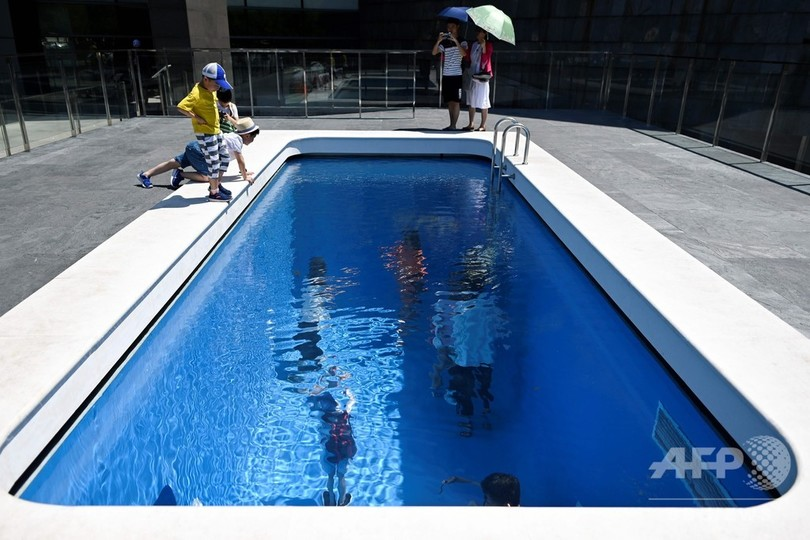 中国・北京の中央美術学院美術館で開催中のレアンドロ・エルリッヒ氏の個展「The Confines of the Great Void」。作品「スイミング・プール」の中を覗く来場者(2019年7月23日撮影)。(c)WANG Zhao / AFP