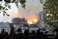 パリの観光名所ノートルダム寺院から立ち上る炎と煙を見る人々(2019年4月15日撮影)。(c)ludovic MARIN / AFP