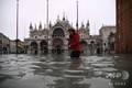 高潮で冠水したイタリア・ベネチアのサンマルコ広場を歩く女性(2019年11月13日撮影)。(c)Marco Bertorello / AFP