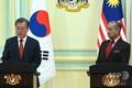マレーシアの首都プトラジャヤで同国のマハティール・モハマド首相(右)と共同記者会見に臨む韓国の文在寅(ムン・ジェイン)大統領(2019年3月13日撮影)。(c)MOHD RASFAN / AFP