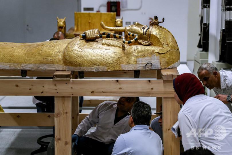 エジプトの首都カイロ郊外にあるギザの「大エジプト博物館」で、ツタンカーメン王が眠る金色のひつぎの修復作業を見学するハリド・アナニ考古相(中央、2019年9月21日撮影)。(c)Mohamed el-Shahed / AFP