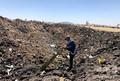 エチオピアのビショフトゥ付近にある墜落現場で、航空機の残骸を調べる男性。エチオピア航空のTwitterの投稿より(2019年3月10日撮影)。(c)AFP PHOTO / TWITTER / ETHIOPIAN AIRLINES